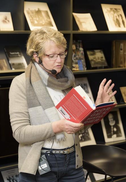 Bibliotekar som står og leser høyt fra en rød bok